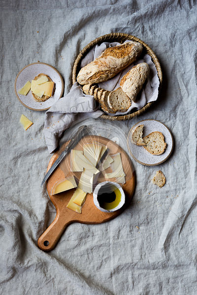 Gluten-Free Baguette, cheese and oil on a gray linen background