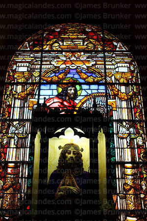 Statue of crucified Christ in front of stained glass window in cathedral, La Paz, Bolivia