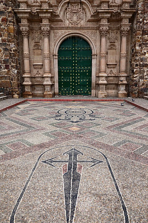 Pebble mosaic cross and main entrance facade of church of Santiago the Apostle / Immaculate Conception, Lampa, Peru