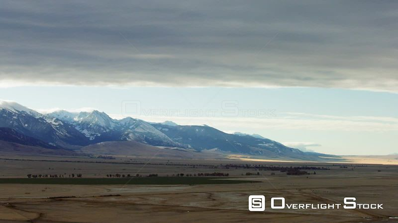 The dawn sun highlights the snowcapped Madison mountain range and the golden autumn colors of the Madison Valley in Southwestern Montana
