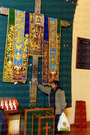 Woman praying at silver cross dedicated to Padre Urraca in La Merced church, Cusco, Peru