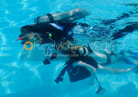 A child learning to scuba dive with an instructor, Salalah, Oman