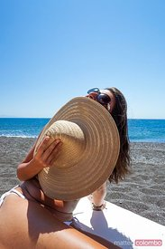 Woman with hat and sunglasses on mediterranean beach, Santorini, Greece