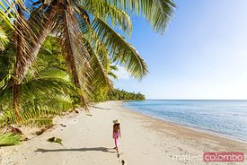 Woman walking on exotic beach with palm trees, Fiji