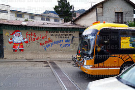 Puma Katari bus driving past Father Christmas mural on wall of the offices of an electricians and electrical workers cooperative, La Paz, Bolivia