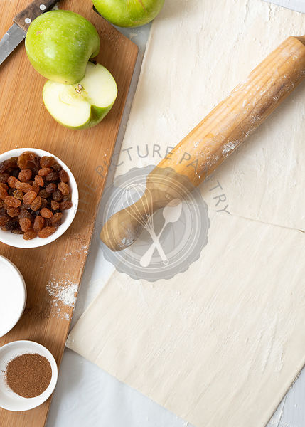 Ingredients for apple studel, including sugar, cinnamon, apples and sultanas on a wooden cutting board with a rolling pin and two pastry sheets.