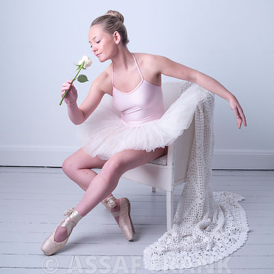 Beautiful young Ballerina sitting on a chair with a Rose