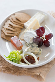 Cheese plate with a selection of cheese and biscuits.