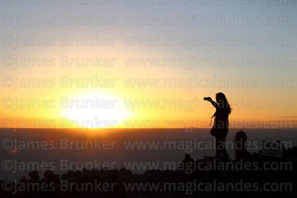 Tourist filming sunrise with mobile phone from summit of Incahuasi Island, Salar de Uyuni, Bolivia