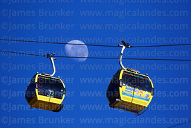 Yellow Line cable car gondolas with Antigripal flu relief advert and almost last quarter waning moon, La Paz, Bolivia