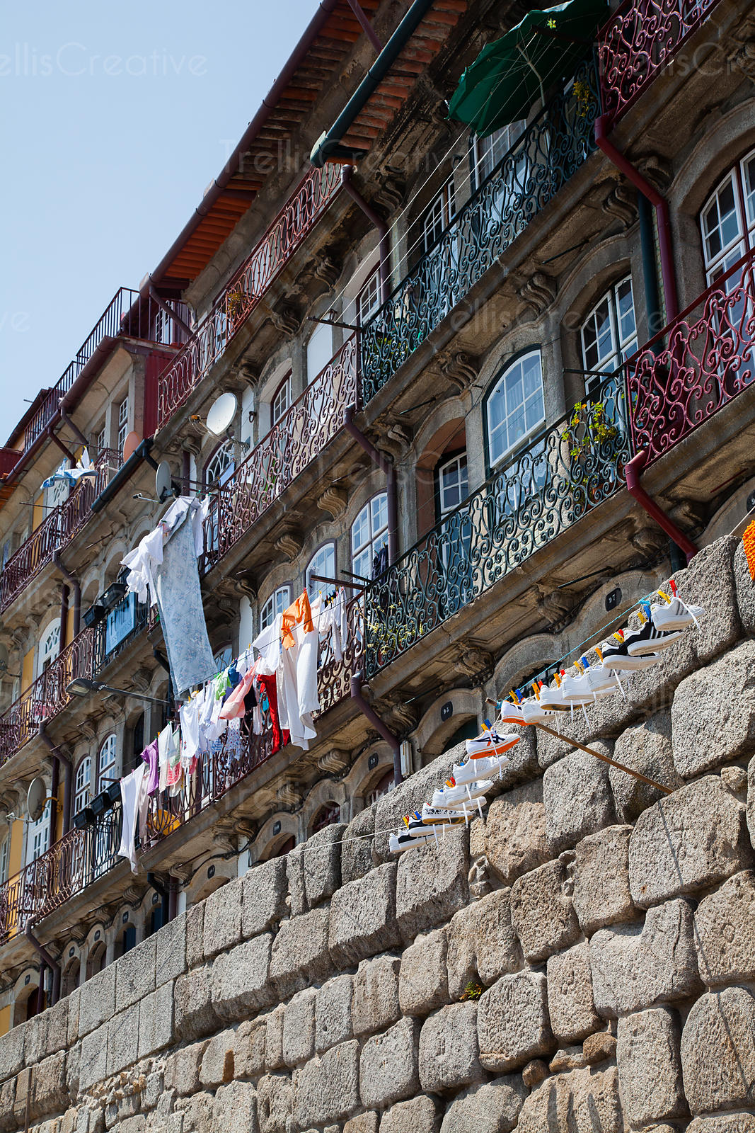 Crisp laundry and clean white sneakers dry outside on drying lines in Riberia district of Porto