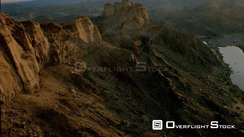 Aerial canted angle wide angle shot side of mountain with cliff face and jagged rocky outcrops, towards and over pinnacle with mountain ranges and partial river in background Fish River Canyon Namibia
