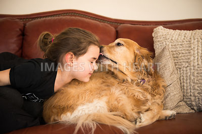 Golden retriever dog giving child kisses on forehead while laying on couch