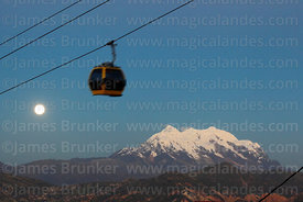 Yellow Line cable car gondola and full moon rising above Mt Illimani, La Paz, Bolivia
