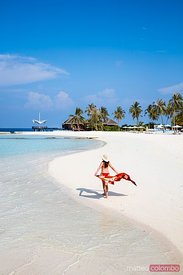 Woman walking on a sandy beach, Maldives