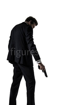 A mystery man in a suit, holding a gun and looking down, in semi-silhouette – shot from low level.