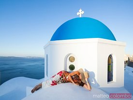 Woman enjoying sunrise on blue domed church, Oia, Santorini, Greece