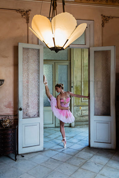 Ballerina in Vintage Tutu Exercising in a Doorway in a Pre-Revolutionary Home
