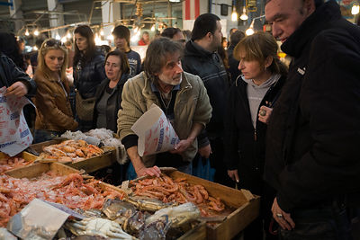 Greece - Athens - A fishmonger serves a woman customerat his stall in the Athens Central Market on Athinas Street