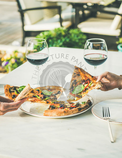 Summer dinner or lunch. People eating freshly baked Italian vegetarian pizza with vegetables and fresh basil and drinking red wine in outdoor restaurant, copy space