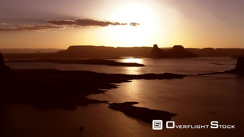 Sunset flight along shore of golden Lake Powell