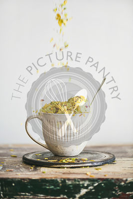 Pistachio ice cream in mug with nuts falling from above
