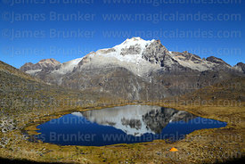 Campsite next to lake with reflection of Mt Huayna Potosí, Cordillera Real, Bolivia