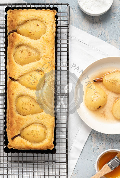 Baked Pear tart cooling on a wire rack with poached pears and a bowl of glaze.