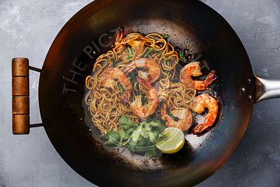 Ramen stir-fry noodles with shrimp in wok pan on gray concrete background close-up