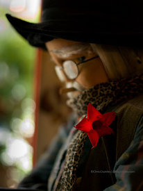 Grizzly little cowboy mannequin in cafe window with freshly picked flower in his lapel, Paris, France