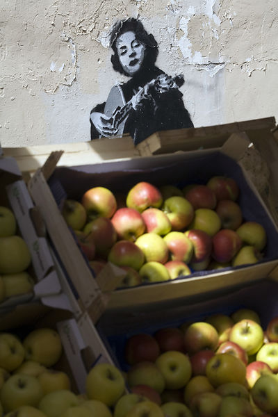 France - Paris - Graffitti and apples on a stall in the market on the Rue Mouffetard.