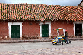 Man pedalling tricycle taxi in front of colonial house, Lampa, Peru