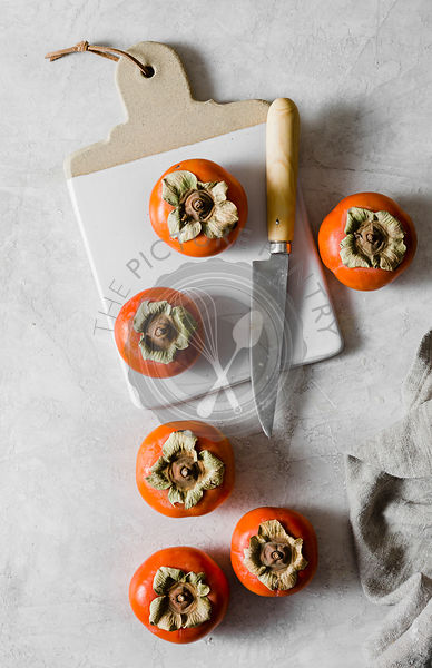 Persimmons on a chopping board and grey marble background