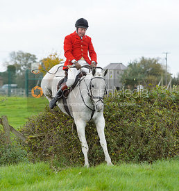 Tom Kingston jumping a hedge near the meet in Long Clawson