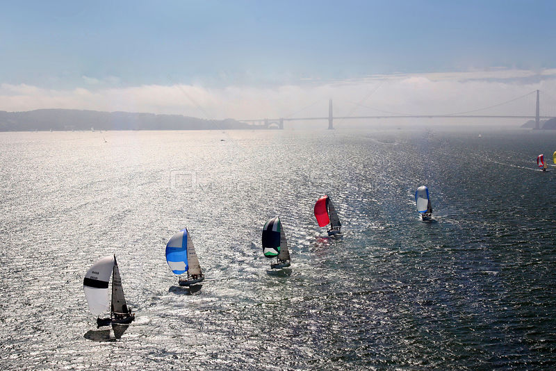 Fleet of yachts with spinnakers, and Bridge in the background. San Francisco to Vallejo Race, San Francisco Bay, California. USA, May 2006.