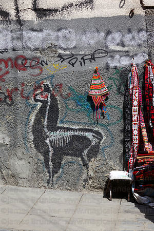Llama graffiti / street art and textile stall in street , La Paz , Bolivia