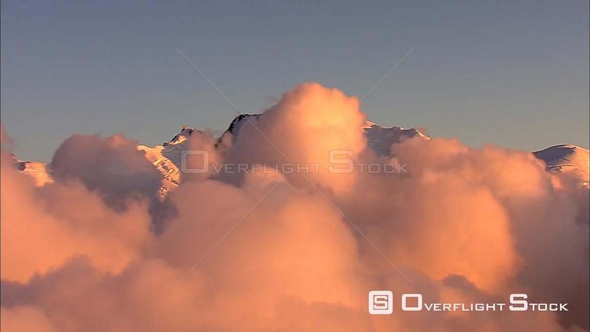 Timelapse puffs of glowing cloud gliding past a peak in the French Alps