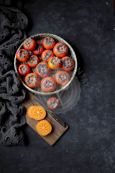 Fresh Persimmons in a bowl, and on a chopping board