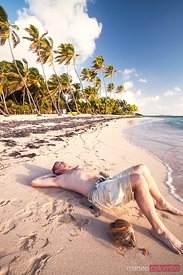Man relaxing on deserted beach at sunrise in the Caribbean