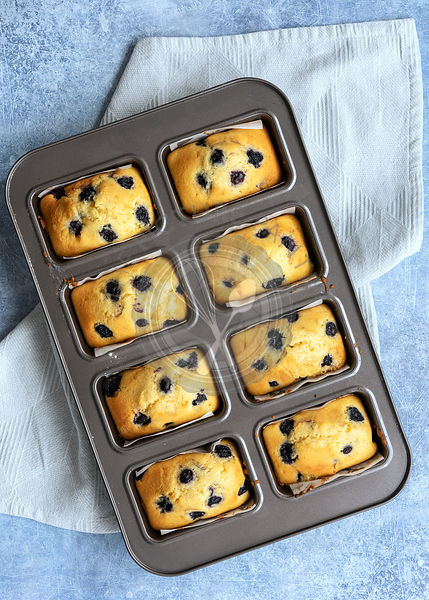 Individual blueberry loaf cakes cooling in a tin.