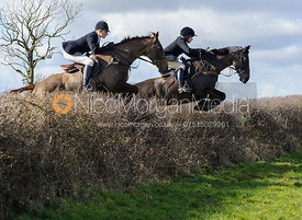 Zoe Gibson and Hilary Butler jumping a hedge behind Ladywood Lodge