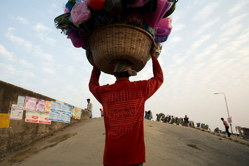 Bangladesh - Chittagong - A man carrying a bowl of clothes on his head walks up a steep slope on the southern shore of the Kalurghat Bridge