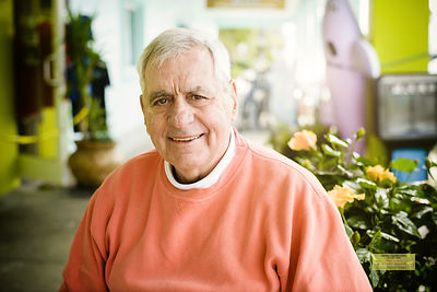 Portrait of a man wearing a salmon colored sweatshirt.