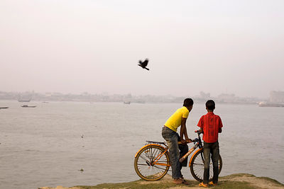 Bangladesh - Chittagong - Two boys, one with a bicycle, watch the river Karnaphuli from the southern bank
