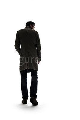 A mystery man in an old coat, walking away, in silhouette – shot from low level.