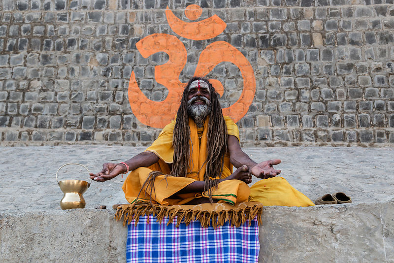 Sadhu Sitting on a Wall in Front of an Orange Om Symbol During Simhasth Kumbh Mahaparv Mela