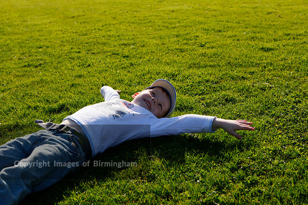 Young boy lying on the grass in the sunshine. Birmingham park.