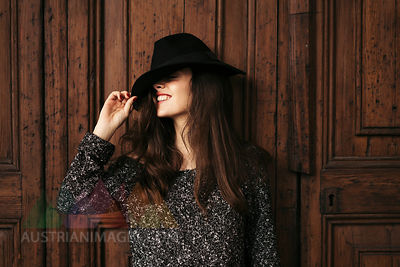 Smiling young woman standing in front of wooden door covering eyes with her hat