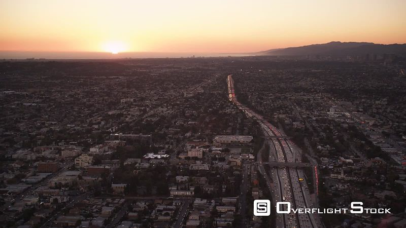 Flying over cityscape and freeways of Los Angeles with sunset in distance. Shot in October