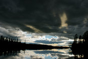 Black cloud over a lake in late afternoon